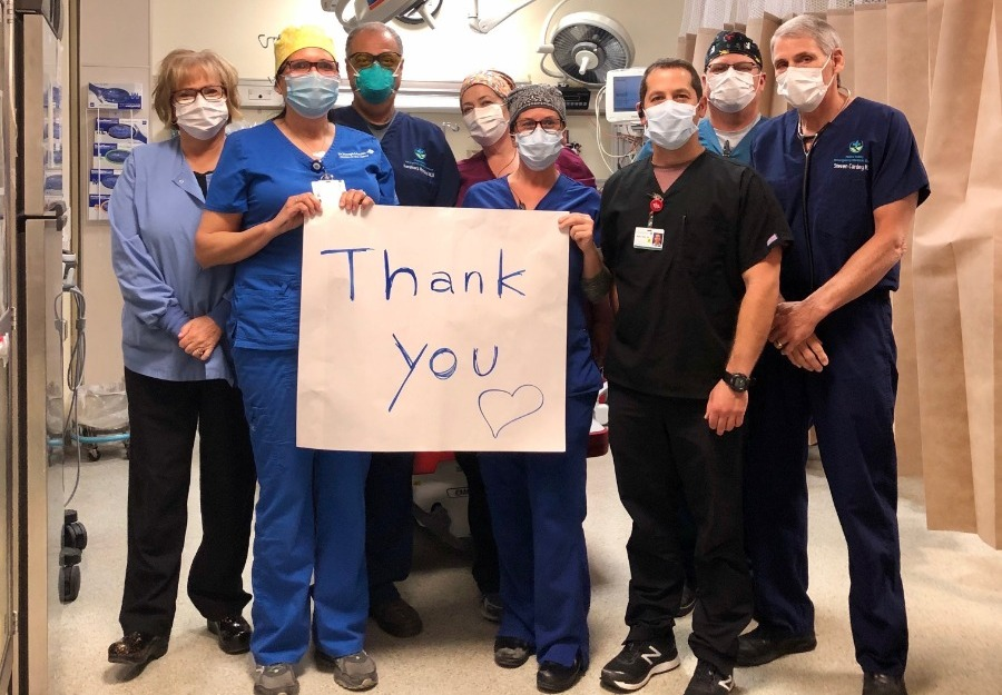 Group of caregivers in scrubs holding Thank You sign