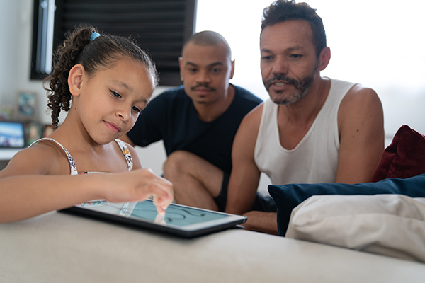 Two dads watching daughter navigate tablet