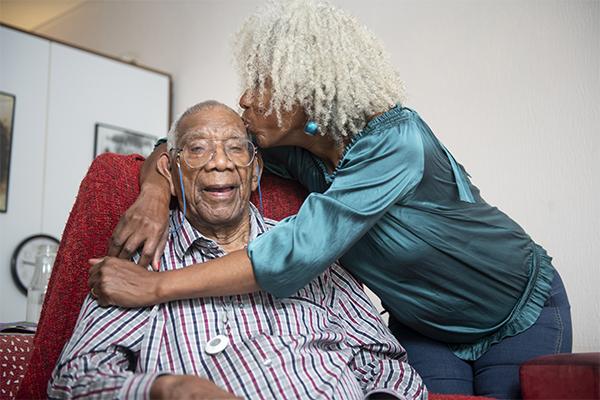 Elderly woman kissing elderly man on forehead