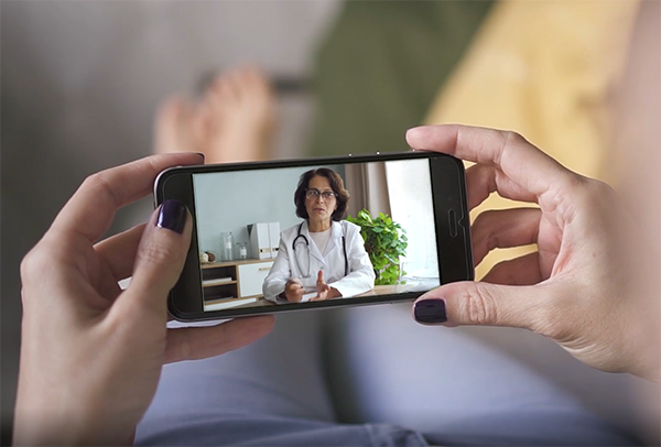 Hands holding mobile phone showing doctor on telehealth call