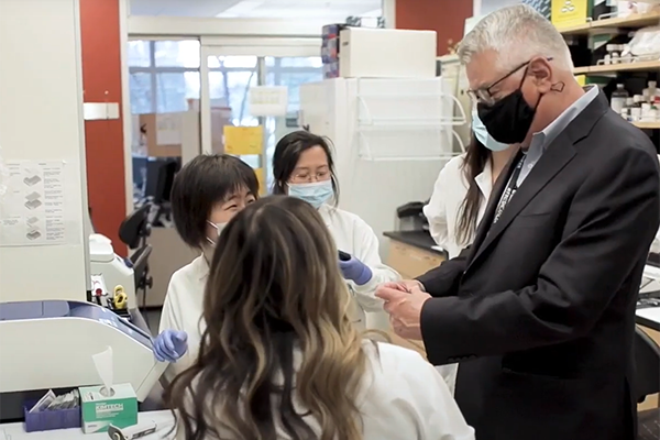 Dr. Urba talks with researchers in lab