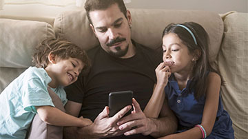 Dad and two kids looking at mobile phone