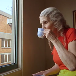 Elderly woman sipping tea while looking out apartment window