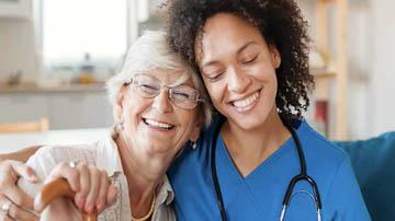 Elderly woman hugging caregiver