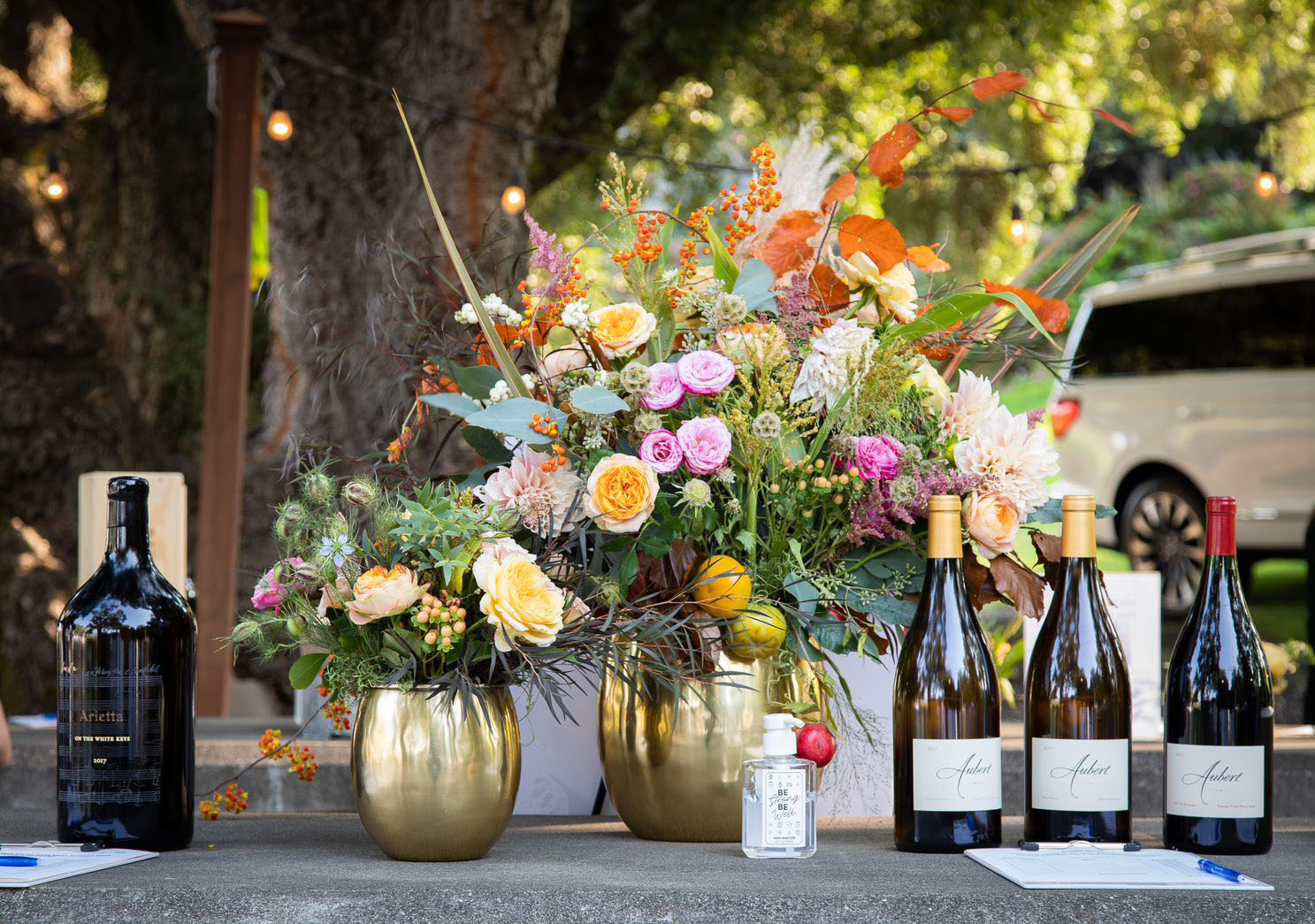 Two floral arrangements and four bottles of wine